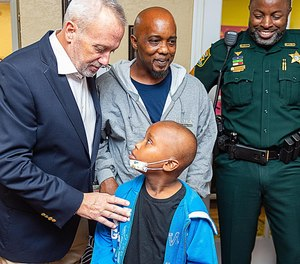 St. Johns County Sheriff David Shoar talks to Arcolia Gilliard Jr., who was surprised by local law enforcement officers with a weeklong trip to Disney World. (Photo/Peter Willott/The Record/TNS)