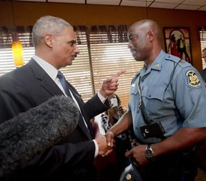 In this Aug. 20, 2014 file photo, Attorney General Eric Holder talks with Capt. Ron Johnson of the Missouri State Highway Patrol at Drake's Place Restaurant in Florrissant, Mo. (AP Image)