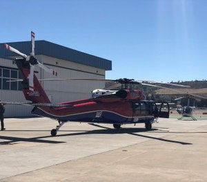 Two UH-60 Black Hawk helicopter equipped with aerial water buckets depart to support fire suppression during a wildfire. (Photo/SDG&E and San Diego County)