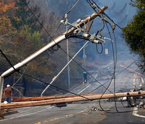 People walk past a fallen transformer and downed power lines on Parker Hill Road in Santa Rosa, Calif.