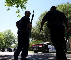Dallas Police walk a neighborhood a block away from a shooting in Dallas.