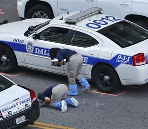 An FBI evidence response team works the crime scene, Sunday, July 10, 2016, where five Dallas police officers were killed Thursday, in Dallas. (AP Image)