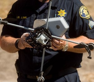 Sgt. Jim Linn retrieves the Alameda County Sheriff's Office drone while demonstrating a search and rescue operation on Friday, Aug. 14, 2015, in Dublin, Calif.