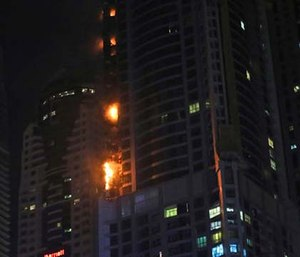 The high-rise residential tower has caught fire in the middle of the night, sending plumes of black smoke into the air and debris falling below. (AP Photo/Kamran Jebreili)