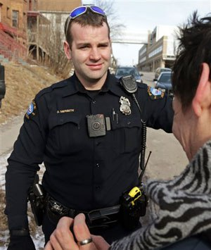 A red light on the body camera worn on Duluth, Minn. police officer Dan Merseth's uniform indicates it is active prior to taking a man, right, to a detox center. (AP Image)