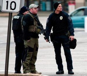 Police officers work the scene where two Bellefontaine Neighbors officers were shot and a man barricaded himself inside a home on Thursday, Dec. 14, 2017, in the St. Louis County town of Bellefontaine Neighbors, Mo. (Robert Cohen/St. Louis Post-Dispatch via AP)