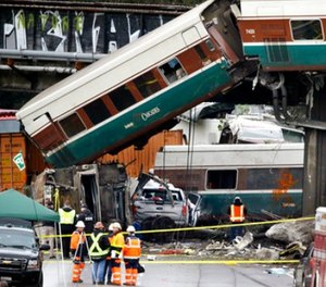 Cars from an Amtrak train lay spilled onto Interstate 5 below alongside smashed vehicles as some train cars remain on the tracks above Monday, Dec. 18, 2017, in DuPont, Wash. (AP Photo/Elaine Thompson)