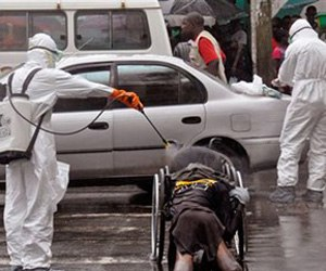 Health workers spray the body of an amputee suspected of dying from the Ebola virus with disinfectant in Liberia. (AP Photo/Abbas Dulleh, File)