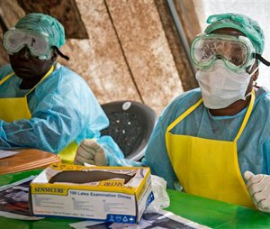 In this Saturday, Aug. 9, 2014 file photo, health workers wearing protective clothing and equipment against the deadly Ebola virus sit in a screening tent at the government hospital in Kenema, eastern Sierra Leone.