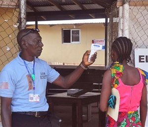 A family member of a 10-year old boy who contracted Ebola has her temperature measured by a health worker before entering the Ebola clinic were the child is being treated. (AP Photo/ Abbas Dulleh)
