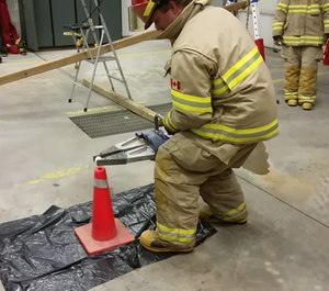 As part of the wedge spreader and eggs fire training drill, firefighters are first asked to pick up small- to medium-size blocks of wood with a hydraulic spreader. (Photo/YouTube)