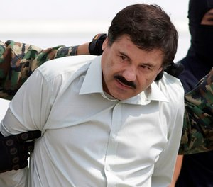 "In this Feb. 22, 2014 file photo, Joaquin ""El Chapo"" Guzman, the head of Mexico's Sinaloa Cartel, is escorted to a helicopter in Mexico City following his capture in the beach resort town of Mazatlan. (AP Photo/Eduardo Verdugo, File)"
