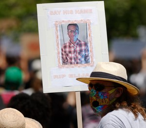 A demonstrator holds a placard during a rally and march over the death of 23-year-old Elijah McClain Saturday, June 27, 2020. (AP Photo/David Zalubowski)