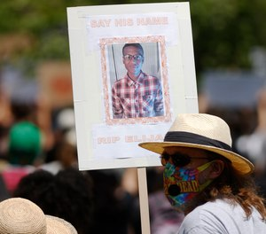 A demonstrator holds a placard during a rally and march over the death of 23-year-old Elijah McClain Saturday, June 27, 2020.