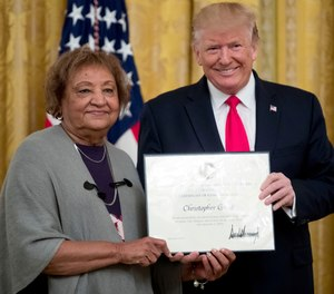 In this Sept. 9, 2019, file photo, President Donald Trump presents a Certificate of Commendation to Minnie Grant, the mother of Christopher Grant, one of five civilians celebrated for their heroism during a mass shooting in El Paso, Texas, at a ceremony in the East Room of the White House in Washington. (AP Photo/Andrew Harnik, File)