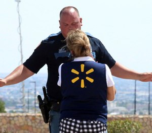 An El Paso police officer talks to a store employee following a shooting at a shopping mall in El Paso, Texas, on Saturday, Aug. 3, 2019.