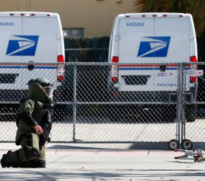 A member of the Miami-Dade County Police Bomb Squad looks for pieces of a suspicious package that was rendered safe after the bomb squad detonated the package that was found by a U.S. Postal employee who noticed what appeared to be wires coming out of an envelope at a post office, Monday, Nov. 5, 2018, in Miami Beach, Fla.