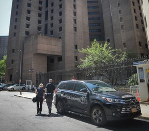 New York City medical examiner personnel leave their vehicle and walk to the Manhattan Correctional Center where financier Jeffrey Epstein died by suicide while awaiting trial on sex-trafficking charges, Saturday Aug. 10, 2019, in New York. (AP Photo/Bebeto Matthews)