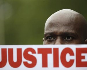 In this July 18, 2015 file photo, a demonstrator holds a sign calling for justice during a rally in New York were several hundred people rallied outside the federal courthouse in Brooklyn to demand action in the fatal chokehold death of Eric Garner by a white police officer.