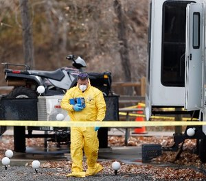 An investigator emerges with evidence from a trailer in a park along Clear Creek in which the body of a 63-year-old man was found Tuesday, Oct. 31, 2017, in Golden, Colo. (AP Photo/David Zalubowski)