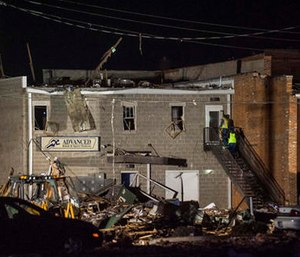 Emergency personnel investigate the damage done from an explosion to Advanced Rehab and Sports Medicine in Canton, Ill. (Lewis Marien/The Journal-Star via AP)
