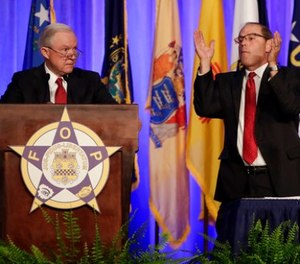 Attorney General Jeff Sessions, left, is applauded by Fraternal Order of Police National President Chuck Canterbury as Sessions addresses the group's convention Monday, Aug. 28, 2017, in Nashville, Tenn.