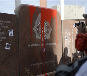 In this photograph taken Saturday, Feb. 14, 2015, protesters take pictures of red paint that was thrown on the memorial to fallen officers in Denver.