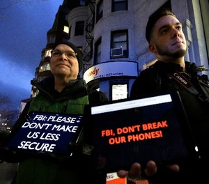 In this Tuesday, Feb. 23, 2016, file photo, demonstrators Peter Brockmann, of Northborough, Mass., left, and Chris Gladney, of Boston, right, display iPads with messages on their screens outside an Apple store in Boston.