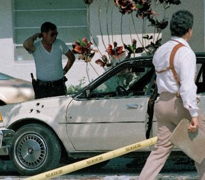 Law enforcement officials survey the scene of a shootout in which two FBI agents were killed and multiple other agents wounded, April 12, 1986.