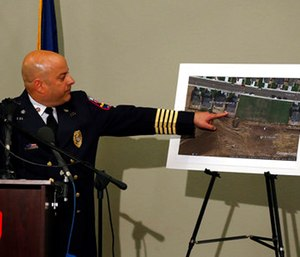 Ted Poszywak, chief of the Frederick-Firestone fire department, points at a picture during a news conference, of the location where an unrefined gas leak explosion killed two people inside their home, in Firestone, Colo. (AP Photo/Brennan Linsley)