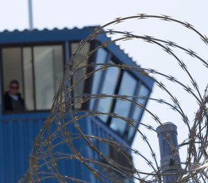 In this Aug. 17, 2011, file photo, concertina wire and a guard tower are seen at Pelican Bay State Prison near Crescent City, Calif.