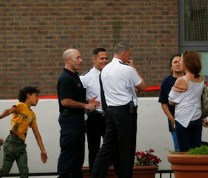 Fire officers talk to residents outside Burnham block, part of the Chalcots Estate in the borough of Camden, after the local council evacuated some 650 homes overnight. (AP Photo/Alastair Grant)