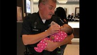 Photo: Officer comforts infant while medics care for mom's seizure