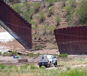 A border patrol vehicle stands guard at a section of collapsed fence just west of the Mariposa Port of Entry in Nogales, Ariz., Sunday, July 27, 2014, after severe storms in southern Arizona over the weekend knocked down a chunk of the metal border fence that divides Mexico and the U.S. Rain runoff from the storms destroyed about 60 feet worth of fence and caused damage to homes just north of it.