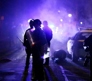 In this Nov. 25, 2014 file photo, police officers watch protesters as smoke fills the streets in Ferguson, Mo.
