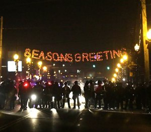 In this Nov. 25, 2014 file photo, protesters gather near the Ferguson Police Department Ferguson, Mo. (AP Image)