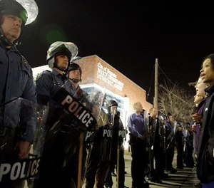 In this March 11, 2015 file photo, police and protesters square off outside the Ferguson Police Department in Ferguson, Mo. (AP Photo/Jeff Roberson, File)