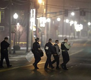 Police canvass the area as they investigate the scene where two police officers were shot outside the Ferguson Police Department Thursday, March 12, 2015, in Ferguson, Mo. (AP Image)