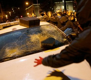 In this Nov. 25, 2014 file photo, protesters vandalize a police vehicle outside of Ferguson city hall in Ferguson, Mo.