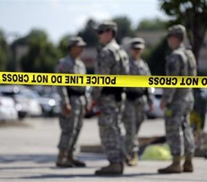 Members of the Missouri National Guard stand guard over a police command post Tuesday, Aug. 19, 2014, in Ferguson, Mo. (AP Image)