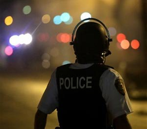 A law enforcement officer watches Sunday, Aug. 17, 2014, after tear gas was fired to disperse a crowd protesting the shooting of teenager Michael Brown last Saturday in Ferguson, Mo. (AP Image)