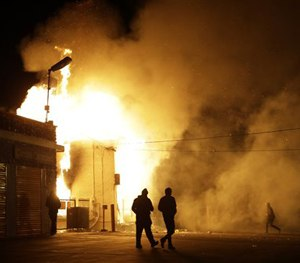 In this Nov. 24, 2014 photo, people walk away from a storage facility on fire after the grand jury decision was announced in Ferguson. (AP Image)