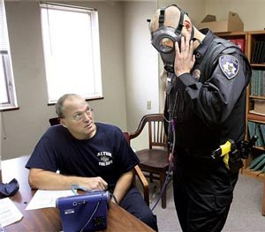 Alton, Ill., Fire Department engineer Bob Eichen, left, uses a machine to run a series of five tests on the gas mask of Alton Police officer Michael Beaber, right, at the Don Twichell Memorial Fire Station in Alton, Monday Nov. 10, 2014. (AP Image)