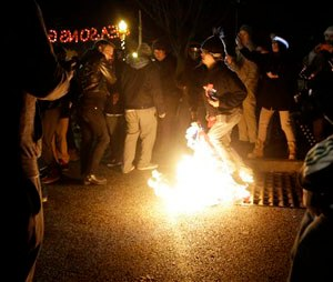 A protester burns an American flag outside the Ferguson Police Department Saturday, Nov. 29, 2014, in Ferguson, Mo. (AP Photo/Jeff Roberson)