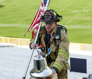 A firefighter rings the bell to remember the fallen during the 2017 9/11 Memorial Stair Climb at Lambeau Field. (Photo courtesy of Pierce Manufacturing)