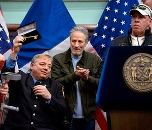 Comedian Jon Stewart joined New York Mayor Bill de Blasio to honor the cancer-stricken Sept. 11 first responder who helped win a fight for health care. (AP Photo/Craig Ruttle)