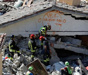 Rescuers mark a building with paint signaling the date and time of start and end of the search operation on that building, following Wednesday's earthquake in Pescara Del Tronto, Italy, Thursday, Aug. 25, 2016. (AP Photo/Gregorio Borgia)