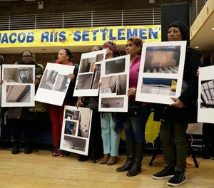 Residents of the Jacob Riis Settlement in New York City hold photographs of leaks, mold, peeling paint and other issues during a community town hall meeting on March 7, 2019.