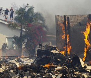 Two people were found dead and scores of houses burned in a pair of wildfires that stretched across more than 100 square miles of Southern California. (Photo/AP)