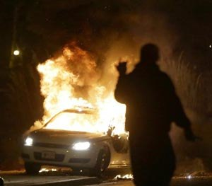 A police car is set on fire after a group of protesters vandalize the vehicle after the announcement of the grand jury decision Monday, Nov. 24, 2014, in Ferguson, Mo. (AP Image)